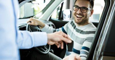 the car dealer handing the keys to the happy customer