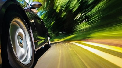 car racing around a turn on a wooded rode auto dealerships customer experience